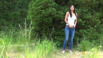 Brazen dark gal in denim Rebecca pees within the wood