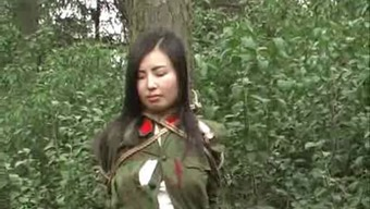 Oriental military girl tied to tree 1(one)