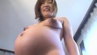 Far eastern preggo performs back with her tits