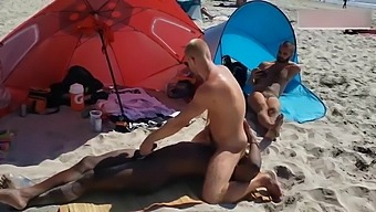 Black and white gay on a public beach. Interracial outdoor
