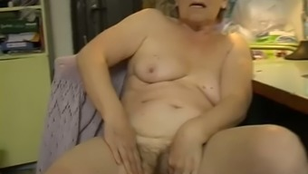 Attractive white colored haired granny masturbates with the use of dildo in bedroom